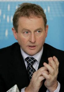 Enda Kenny attempts to add up the number of ministerial posts available using his body as an abacus.