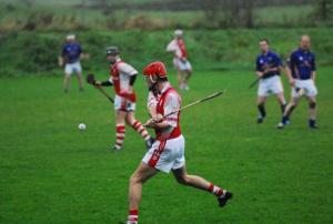 A Leitrim hurler attempts to rise the ball and hit it while the others offer encouragement.