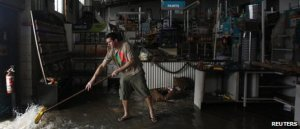 A local man nonchalantly pushes the biblical flood out of his shop with an old broom.